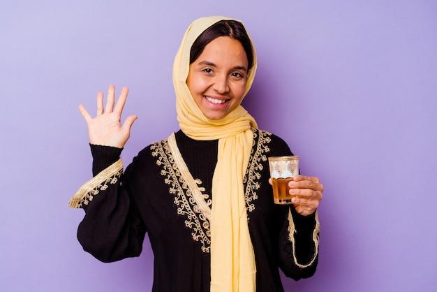 Jonge marokkaanse vrouw die een glas thee houdt dat op purpere achtergrond wordt geïsoleerd glimlachend vrolijk tonend nummer vijf met vingers.