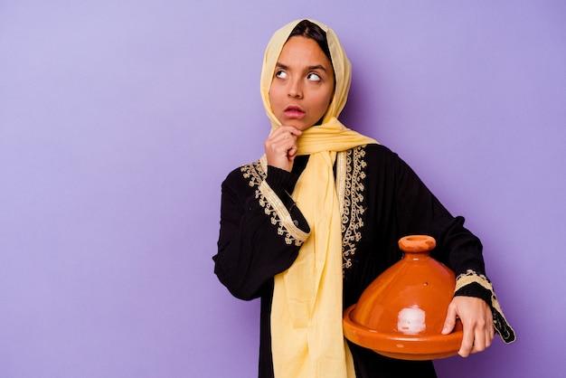 Jonge marokkaanse vrouw die een tajine houdt die op paarse achtergrond wordt geïsoleerd en zijwaarts kijkt met een twijfelachtige en sceptische uitdrukking.