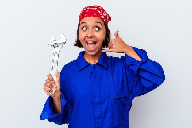 Jonge mechanische vrouw die een geïsoleerde sleutel houdt die een mobiel telefoongesprekgebaar met vingers toont