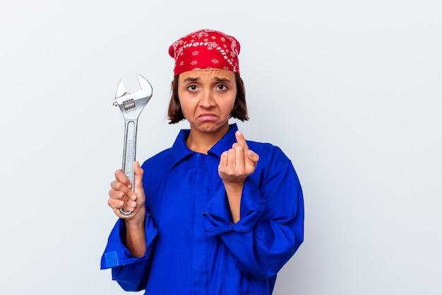 Jonge mechanische vrouw die een geïsoleerde sleutel houdt die met vinger naar u richt alsof uitnodigend naderbij komt.