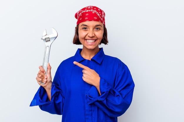 Jonge mechanische vrouw die een sleutel houdt die geïsoleerd glimlacht en opzij wijst, iets op lege ruimte toont.
