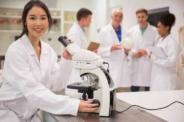 Jonge medische student die met microscoop werkt