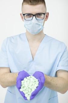 Jonge medische werker met bril en beschermend masker houdt handvol pillen geïsoleerd op een witte muur