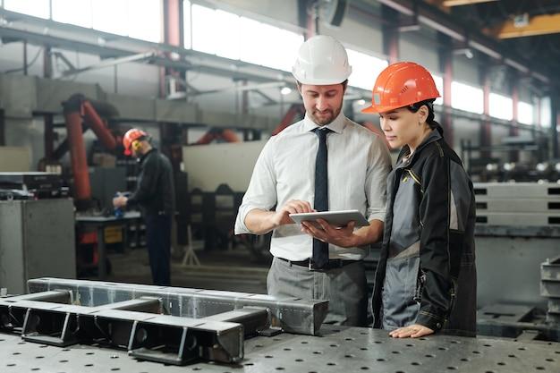 Jonge meester in veiligheidshelm wijzend op gegevens of technische schets op het beeldscherm van de tablet terwijl hij zijn ondergeschikte per werkplek raadpleegt
