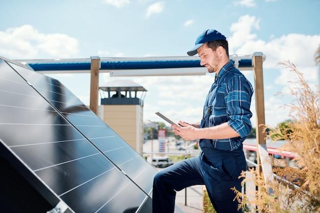 Jonge meester met tablet op zoek naar online gegevens over de installatie van zonnepanelen terwijl hij op het dak staat