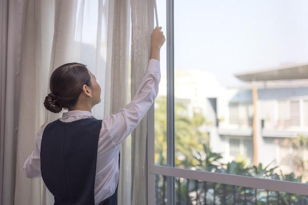 Jonge meid gordijnen in hotelkamer openen