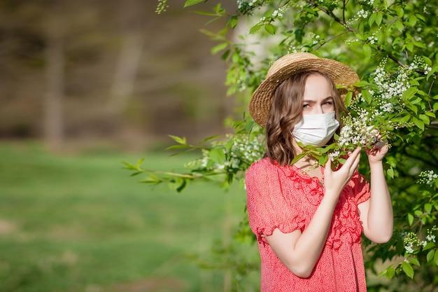 Jonge meisjes blazende neus en niezend in weefsel voor bloeiende boom. seizoensgebonden allergenen die mensen treffen. mooie dame heeft rhinitis.