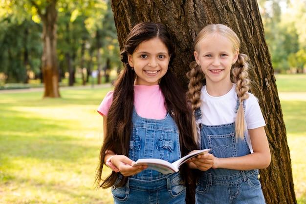 Jonge meisjes die boek houden en camera bekijken