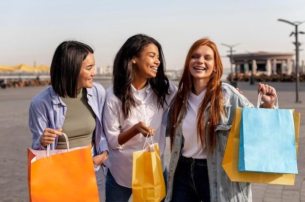 Jonge meisjes die een wandeling maken na het winkelen