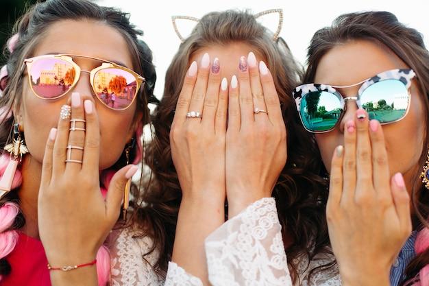 Jonge meisjes die in zonnebril dragen die gezicht door handen verbergen.