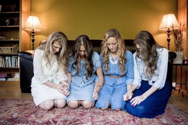 Jonge meisjes die naast elkaar in een kamer neerkijken