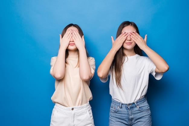 Jonge meisjes die ogen behandelen door handen die op blauwe muur worden geïsoleerd