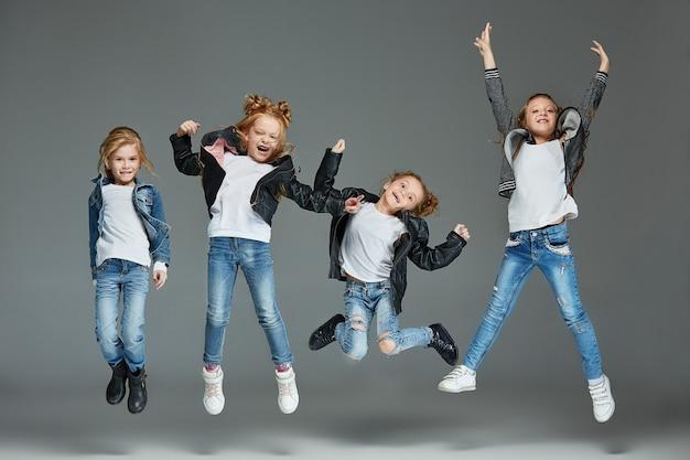 Jonge meisjes die op grijze studioachtergrond springen