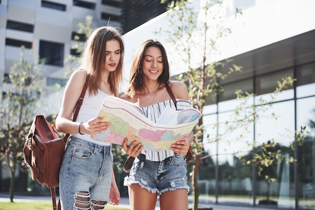Jonge meisjes die stadsplattegrond lezen en een hotel zoeken. mooie toeristen met rugzakken bepalen het concept van kennis van de wereld.
