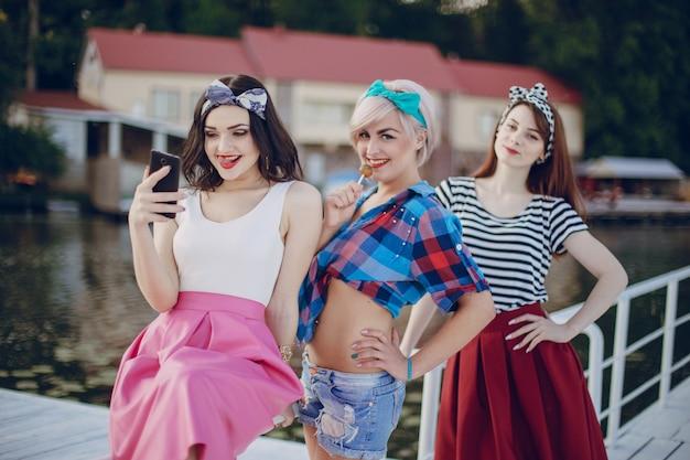 Jonge meisjes die zich voordeed op een witte balustrade en te kijken naar haar mobiele telefoon