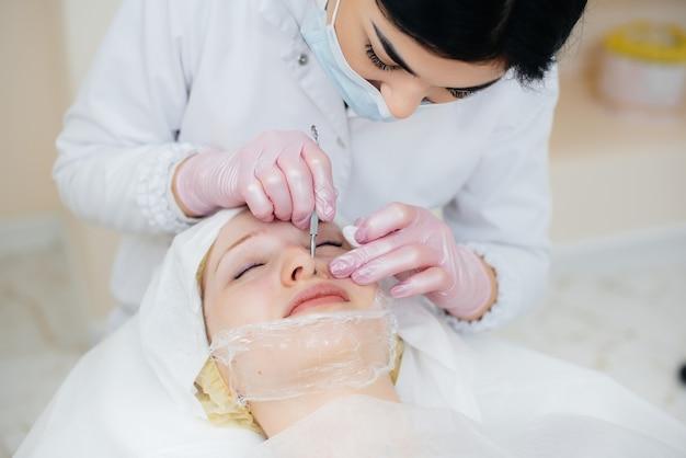 Jonge meisjes doen mechanische gezichtsreiniging in een moderne cosmetologie-kliniek. cosmetologie.