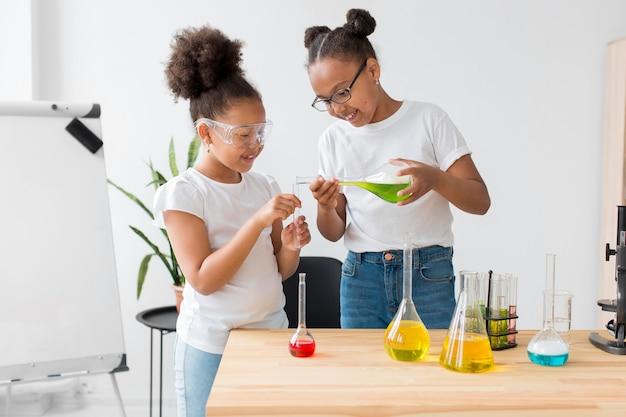Jonge meisjes experimenteren met drankjes terwijl ze een veiligheidsbril dragen