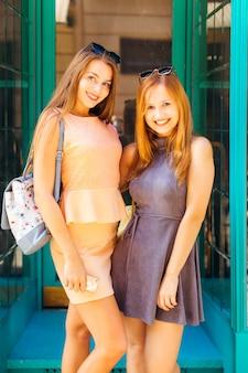 Jonge meisjes in mooie jurken en rugzakken op hun schouders kijken naar de camera en glimlachen schattig