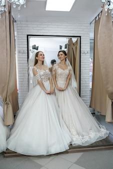 Jonge meisjes in trouwjurken poseren in salon