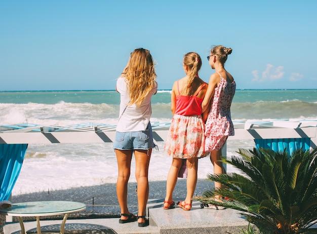Jonge meisjes kijken naar de stormachtige zwarte zee