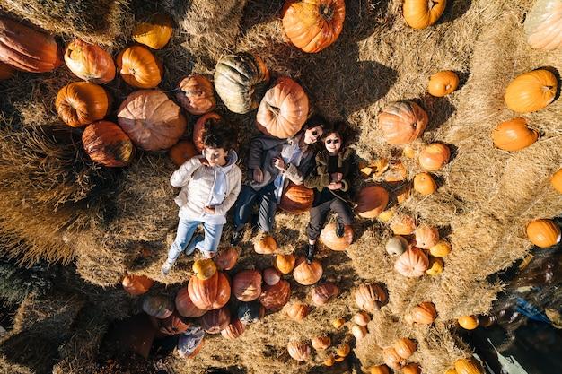 Jonge meisjes liggen op hooibergen tussen pompoenen. uitzicht van boven