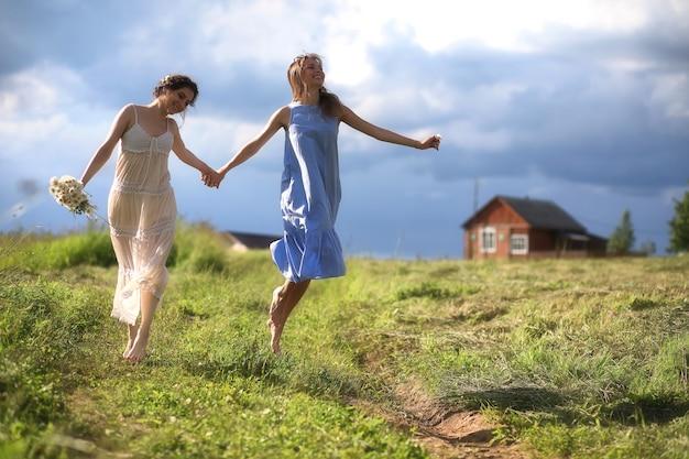 Jonge meisjes lopen in het veld voor de regen