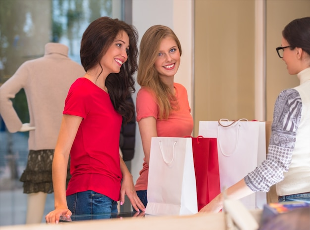 Jonge meisjes met boodschappentassen in de winkel voor contanten