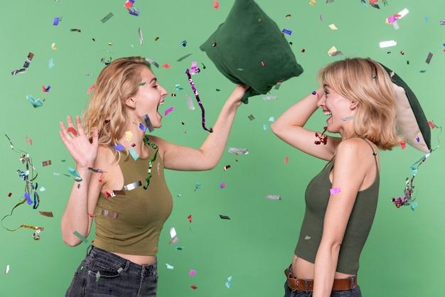 Jonge meisjes met een kussengevecht