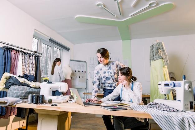 Jonge meisjes mode-ontwerpers met behulp van moderne laptop en het tekenen van schetsen voor nieuwe collectie kleding tijdens het werken aan tafel in de studio. vrouw naaister het nemen van mannequin metingen met maatregel tape