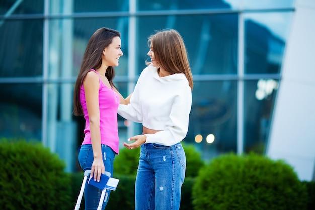 Jonge meisjes ontmoeten elkaar op de luchthaven