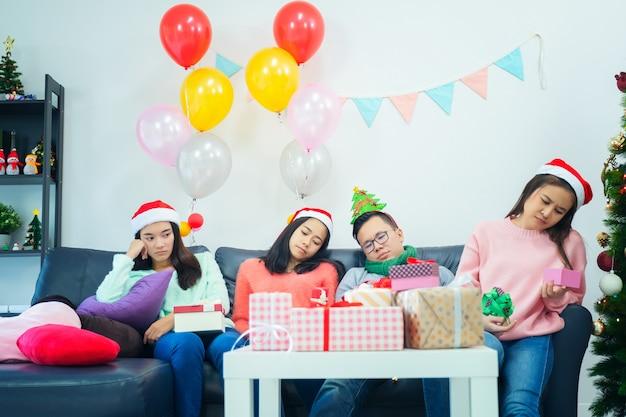 Jonge meisjes openen geschenkdoos dag thuis ontevreden voelen. chagrijnige meisjes in kerstmutsen die kleding kopen bij de kerstverkoop, jaloerse en eenzame emotie