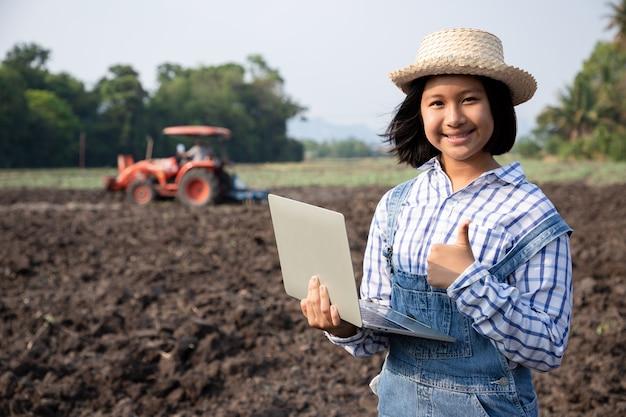 Jonge meisjes overlegden en planden het planten van maïs of sperziebonen met behulp van een computergestuurde laptop in het rijstveld tegen de achtergrond terwijl vader de grond ploegde met een tractor op de boerderij