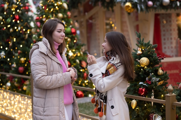 Jonge meisjes reizen op de kerstmarkt in moskou, lopen tegen de achtergrond van licht