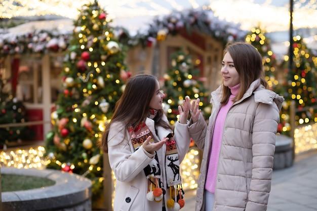 Jonge meisjes reizen op de kerstmarkt in moskou, lopen tegen de achtergrond van lichtjes en kerstbomen, praten, discussiëren en lachen.