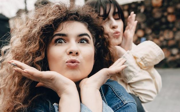 Jonge meisjes spelen samen grappige gezichten terwijl ze buiten poseren