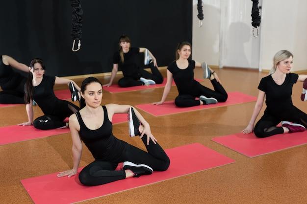 Jonge meisjes sporten in de sportschool op matten, ze doen rekoefeningen. flexibele meisjes in zwarte sportkleding doen yoga.