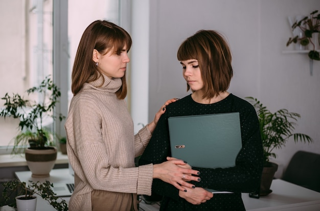 Jonge meisjes tweelingzusjes op het werk. de vrouw is van streek en haar collega troost haar. moeilijkheden op het werk.