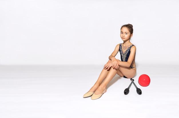 Jonge meisjesatleet zit in de buurt van ritmische gymnastiekapparatuur en kijkt naar de camera