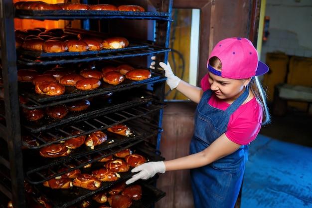 Jonge meisjesbakker houdt een dienblad met warme gebakjes tegen de achtergrond van een industriële oven in een bakkerij. productie van bakkerijproducten. vers krokant gebaksrek