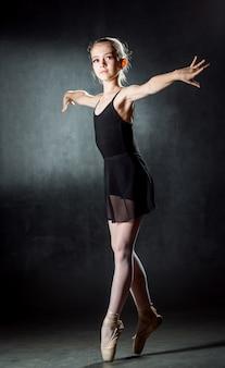 Jonge meisjesballerina die de danselementen op een darkwallballet tonen.