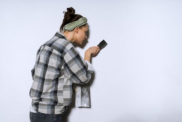 Jonge meisjesbouwer die de muren bekleedt met een spatel en reparaties uitvoert