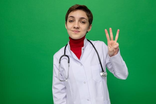 Jonge meisjesdokter in witte jas met stethoscoop om nek kijkend naar voorkant gelukkig en positief glimlachend zelfverzekerd tonend nummer drie met vingers die over groene muur staan