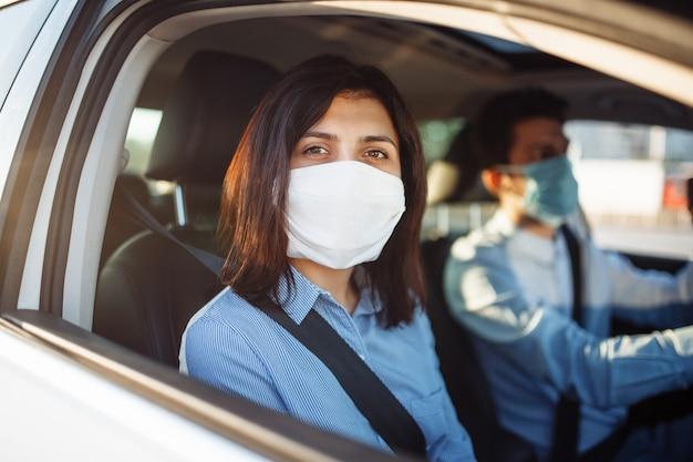 Jonge meisjespassagier maakt een ritje met de taxi tijdens de coronaviruspandemische quarantaine.