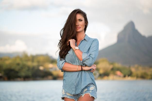 Jonge meisjesreiziger staat op het strand tegen de berg en geniet van de schoonheid van het zee-landschap. jong meisje houdt van het wilde leven, reizen, vrijheid.