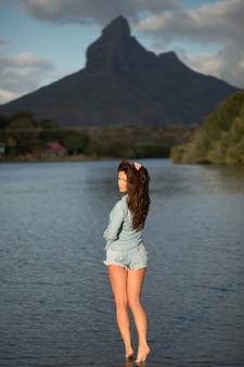 Jonge meisjesreiziger staat op het strand tegen de berg en geniet van de schoonheid van het zee-landschap.