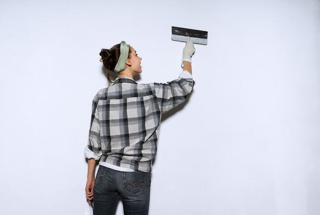 Jonge meisjesschilder in een geruit hemd egaliseert de muren met een spatel, repareert in het appartement