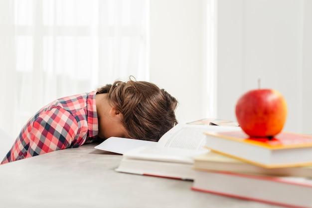 Jonge meisjesslaap in plaats van het bestuderen