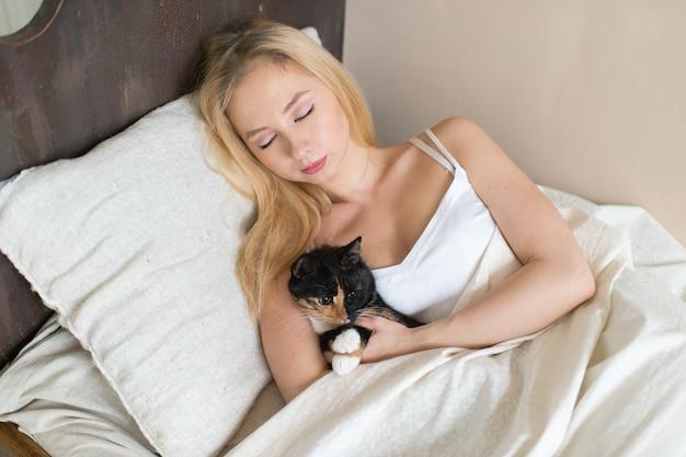 Jonge meisjesslaap op bed met mooi katje