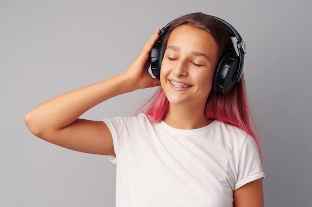 Jonge meisjestiener die aan muziek met haar hoofdtelefoons luistert