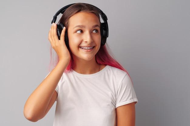 Jonge meisjestiener die aan muziek met haar hoofdtelefoons over een grijze achtergrond luistert